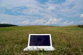 White Laptop In The Grass With Cloudy Sky