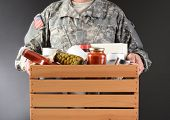 Closeup of a soldier in fatigues holding a wooden box full of canned and packaged food for a holiday