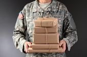 Closeup of a soldier wearing camouflage fatigues holding a stack of packages for mail call. Horizont