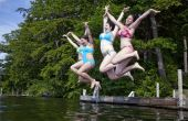 Four Teenage Girls Jumping Off A Dock Into A Lake