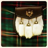 Traditional Scottish sporran over tartan background. Retro style photo.