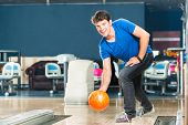 Young man in bowling alley having fun, the sporty man playing a bowling ball in front of the ten pin