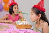 Girl blowing noisemaker while her sister blow the birthday candles at a party
