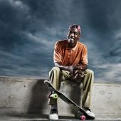 cool african skate boarder sitting down to rest