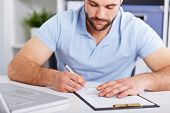 Young Businessman In Blue Polo Shirt Signs A Contract