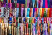 Various of colorful fabrics and shawls at a market stall