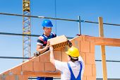 Two Bricklayer or builder or worker build or bricklaying or laying a stone or brick wall on construc