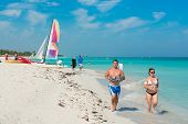 VARADERO,CUBA - APRIL 26,2014: Young people running along the shore and enjoying the beach on a beautiful sunny day