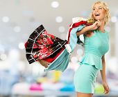 Smiling blond woman choosing clothes in a shopping mall