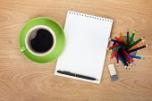 Blank notepad with office supplies and coffee cup on wooden table. Above view