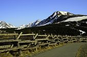 Log fence with mountain and trail