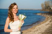 Beautiful Bride In A White Dress On Coast Of River