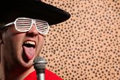 foto of crazy hat  - Crazy rock and roller singer with a big black hat - JPG