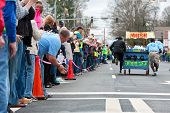 Spectators Cheer Team Pushing Bed Toward Finish Of Fundraiser Race