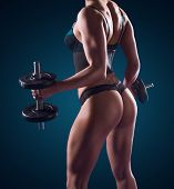 Dark portrait of the torso of a fit muscular athletic woman working out with weights in lingerie showing off her physique and firm buttocks
