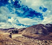 Vintage retro effect filtered hipster style travel image of Bulldozer on road in Himalayas. Ladakh, Jammu and Kashmir, India