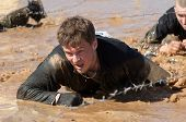 man crawling on a mud puddle