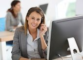 foto of smiling  - Smiling customer service representative at work - JPG