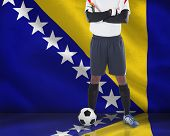 Goalkeeper in white looking at camera against digitally generated bosnian flag