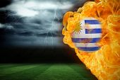 Composite image of fire surrounding uruguay flag football against football pitch under stormy sky