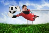 Fit goal keeper jumping up and saving ball against field of grass under blue sky