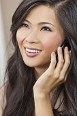 Beautiful young Asian Chinese woman or girl in her twenties talking on a smart cell phone