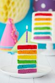 Rainbow cake decorated with a single candle