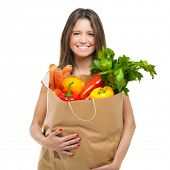 Young woman holding a bag full of vegetables