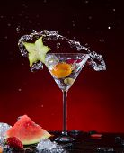 Fresh fruit cocktail in freeze motion splashing, close-up.