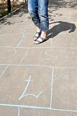 Girl Playing In Hopscotch On Urban Alley