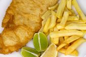 stock photo of hake  - Overhead view of traditional fish and chips meal with chips battered fish and lemon and lime wedges - JPG