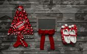 Wooden christmas background with red decoration and an empty advertising sign.