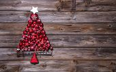 Christmas tree of red balls on wooden background.