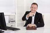 Happy young businessman sitting in his office give advice for customers.