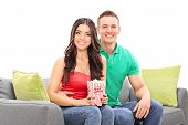 Young couple sitting on couch with box of popcorn isolated on white background
