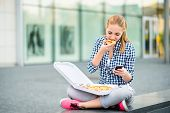 Teenager eating pizza looking in phone