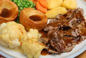 Traditional Sunday roast dinner with Yorkshire puddings and gravy.