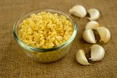 Finely Chopped Garlic With Cloves In The Background