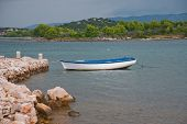 Small White Blue Boat Moored To The Stone Jetty