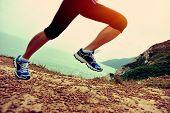 young woman hiker legs walking on seaside mountain trail