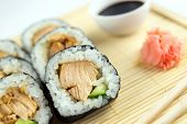 Closeup Of Teriyaki Chicken Sushi Rolls With Cucumber, Chopsticks, Ginger And Soy Sauce