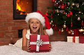 Happy little girl with Christmas present laying by the fire in front of xmas tree