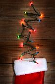 High angle shot of a Christmas stocking on a rustic wood surface with holiday lights sticking out the top. Vertical format.