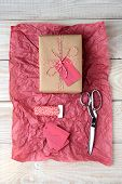 High angle shot of a plain brown paper wrapped present tied with red and white string. The gift is on a piece of red tissue paper with scissors, roll of string and gift tags on a white wood table.