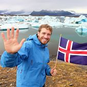 Iceland travel tourist showing Icelandic flag by Jokulsarlon. Man hiker happy holding showing Icelandic flag in front of the glacial lake / glacier lagoon. Happy male smiling in tourism concept.