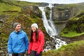 Hiking active couple fun by waterfall in Iceland nature. People walking talking smiling happy in Icelandic tourist landscape in summer. Hiking couple laughing.