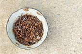 Rusty Metal Nails In A Bowl On The Concrete Surface