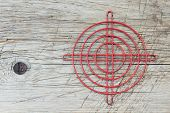 Red Metallic Crosshair On An Old Wooden Surface