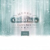 Abstract winter background in shades of silver blue with snowfall and little shiny stars. A label with Merry Christmas and Happy New Year makes and light effects it a festive background for Christmas.
