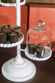 foto of bonbon  - Chocolate bonbons in dish and cocoa on background - JPG